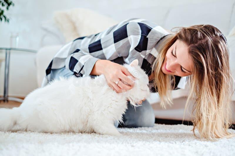 使用与她的白色猫的女孩 库存照片