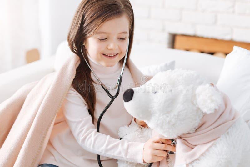 使用与她的蓬松玩具的快乐的小女孩 免版税库存照片