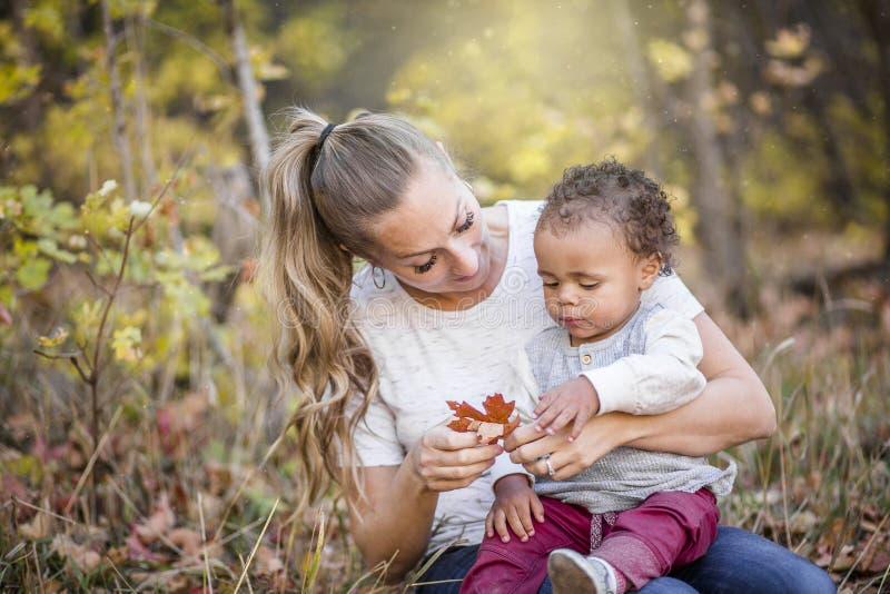 使用与她逗人喜爱的两种人种的儿子的母亲的美丽的坦率的画象 免版税库存照片