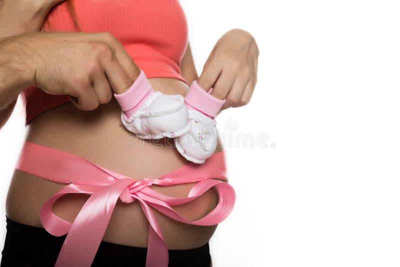 使用与婴孩赃物的内衣的怀孕的妈咪 有桃红色丝带的腹部 慢的行动 免版税图库摄影