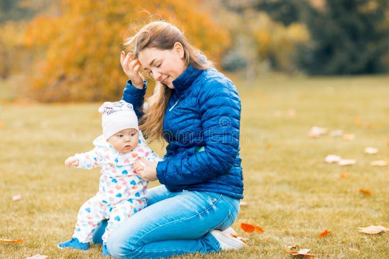 使用与孩子的愉快的微笑的母亲在温暖的秋天天 免版税库存图片