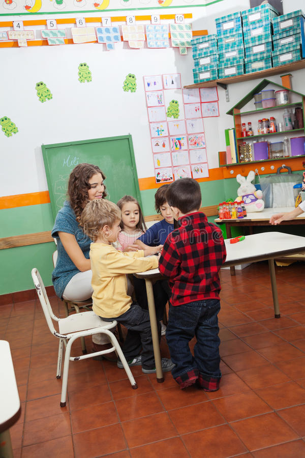 使用与孩子的老师在幼儿园 库存照片