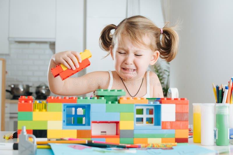 使用与小家家建设者的迷人的学龄前儿童 使用与连接的玩具立方体的小女孩 免版税库存图片