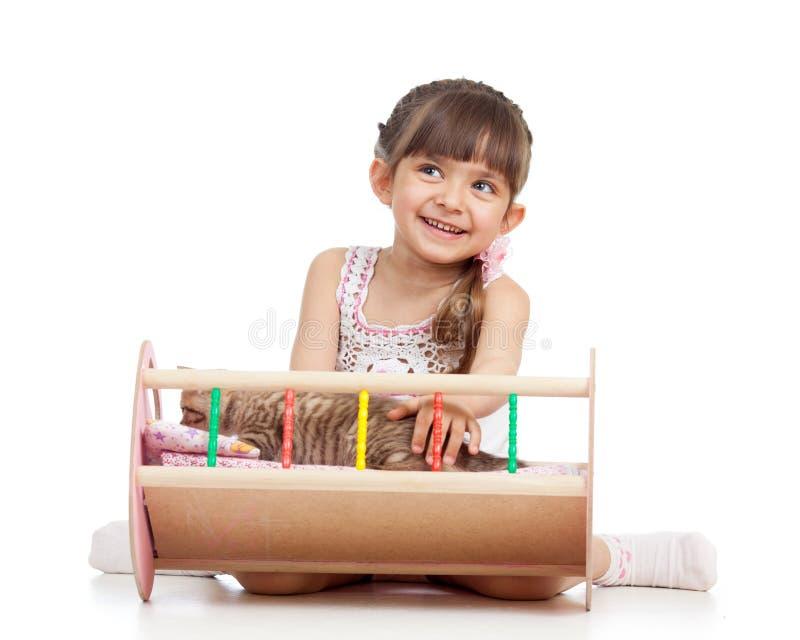 使用与小猫和晃动他的儿童女孩在玩偶小儿床 免版税库存照片