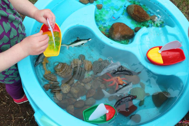 使用与小船和海生物/海洋生活玩具的孩子在水位里 免版税库存图片