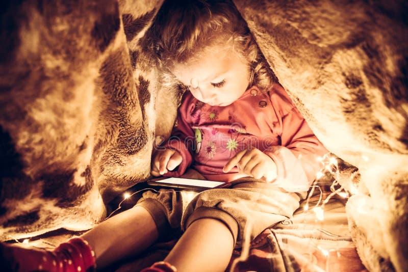 使用与巧妙的电话的孩子掩藏在秘密地方在毯子下从父母 图库摄影