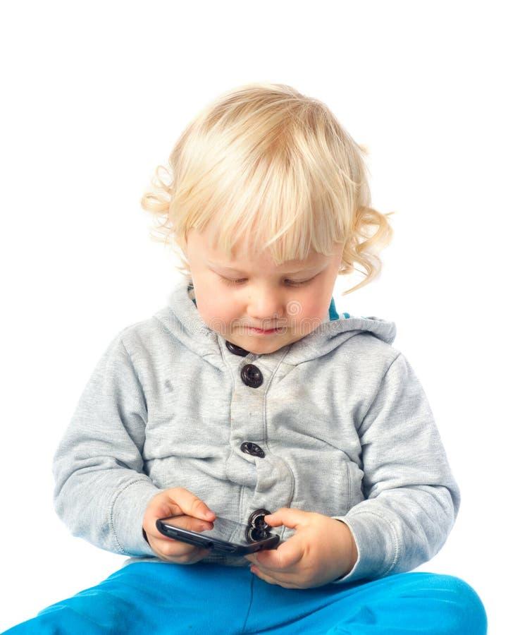 使用与巧妙的电话的小男孩 免版税库存照片