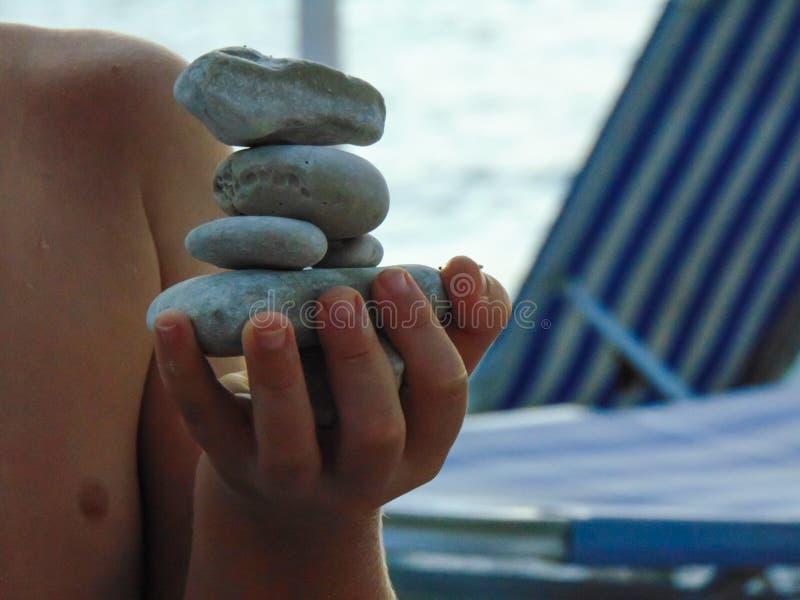 使用与平衡的石头的孩子 库存照片