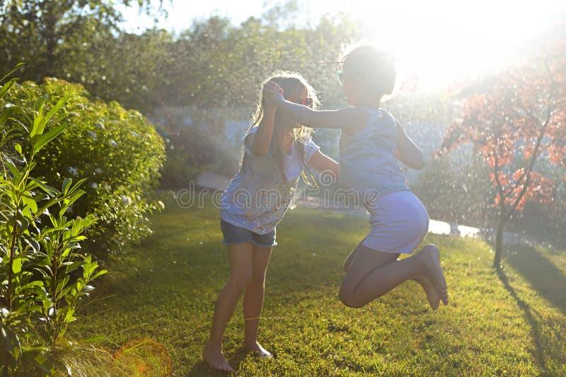 使用与庭院喷水隆头的孩子 孩子跑并且跳 夏天室外水乐趣在后院 儿童游戏用水管水 免版税库存图片
