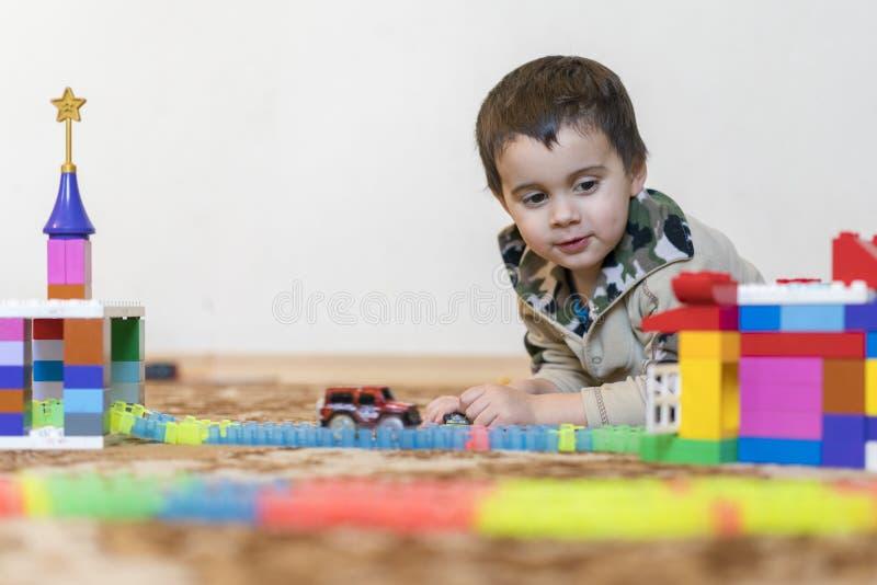 使用与建设者玩具的小微笑的男孩 演奏智力玩具的男孩 免版税库存图片