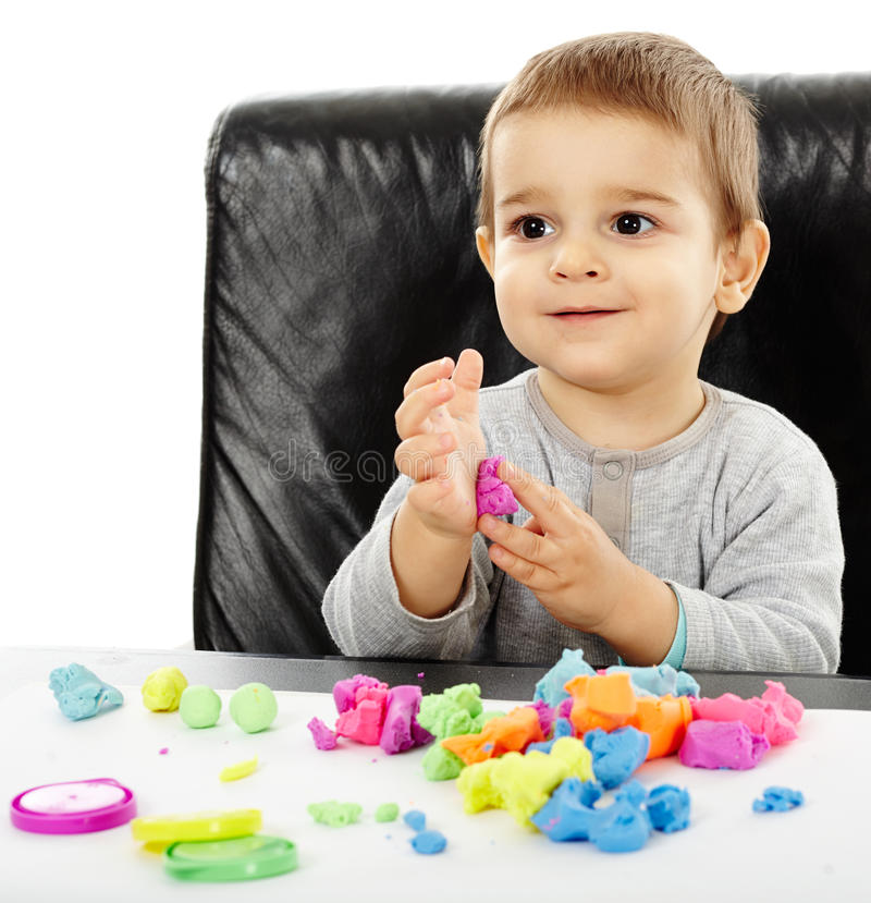 使用与彩色塑泥的小男孩 免版税图库摄影