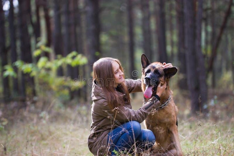 使用与德国牧羊犬狗的年轻可爱的妇女户外在秋天公园,关闭  免版税图库摄影