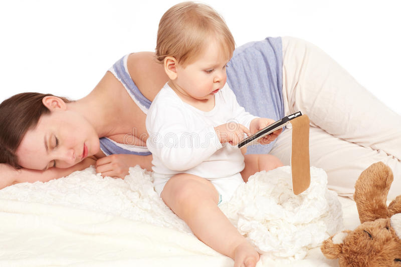 使用与您的智能手机的孩子,当母亲睡觉时 库存照片