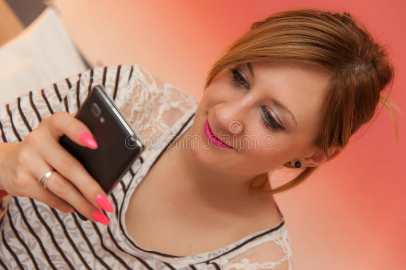使用与手机的女孩 免版税库存图片