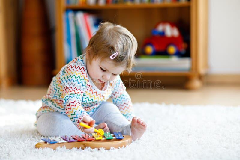 使用与教育木音乐的可爱的逗人喜爱的美丽的矮小的女婴在家戏弄或托儿所 小孩与 免版税库存图片