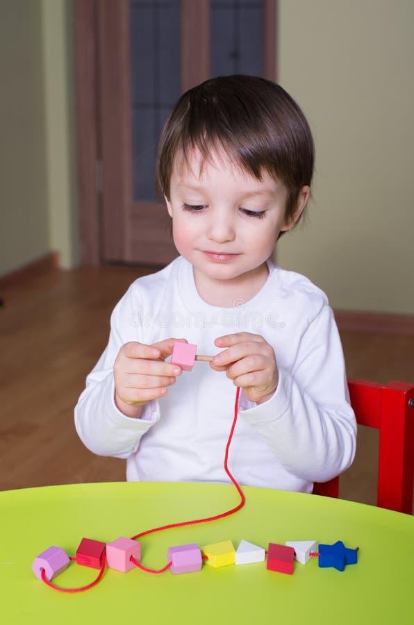 使用与教育玩具成串珠状的孩子 免版税库存照片