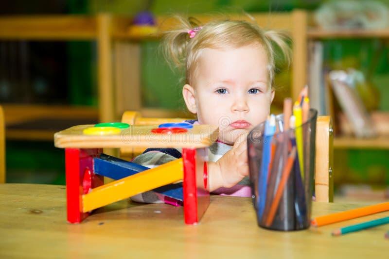 使用与教育玩具的可爱的儿童女孩在托儿所屋子里 孩子在幼儿园在蒙台梭利幼儿园类 免版税库存照片