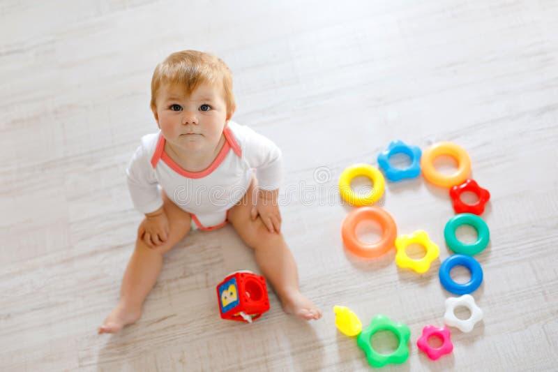 使用与教育玩具的可爱的女婴在托儿所 获得愉快的健康的孩子与五颜六色的不同的玩具的乐趣 库存照片