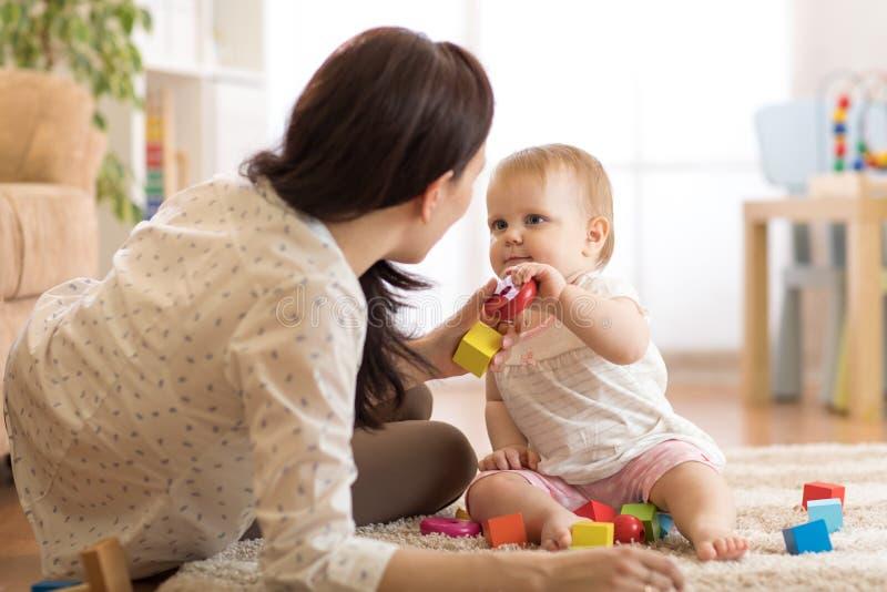 使用与教育玩具的可爱的女婴在托儿所 获得的孩子与五颜六色的不同的玩具的乐趣在家 免版税图库摄影