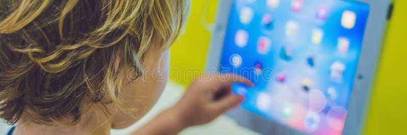 使用与数字式片剂的横幅男孩 孩子和技术 免版税库存图片