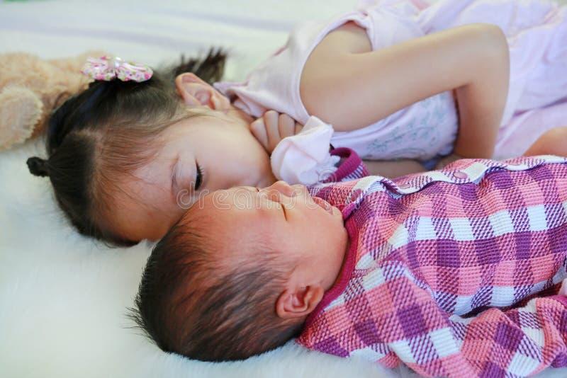 使用与新生儿的亚裔姐妹说谎在白色毛皮背景 免版税库存图片