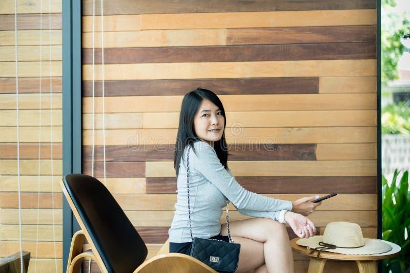 使用与智能手机的亚裔妇女自由wifi在旅馆,搜寻或者人脉,美丽的女性 库存图片