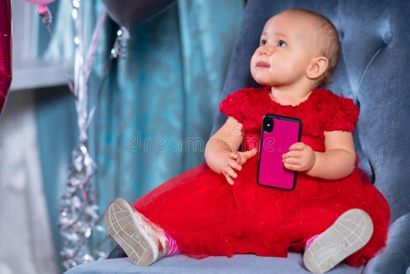 使用与智能手机的逗人喜爱的矮小的女婴 库存照片