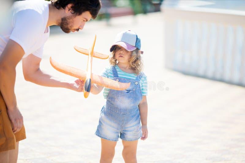 使用与有她的父亲的橙色玩具飞机的可爱的女孩 图库摄影