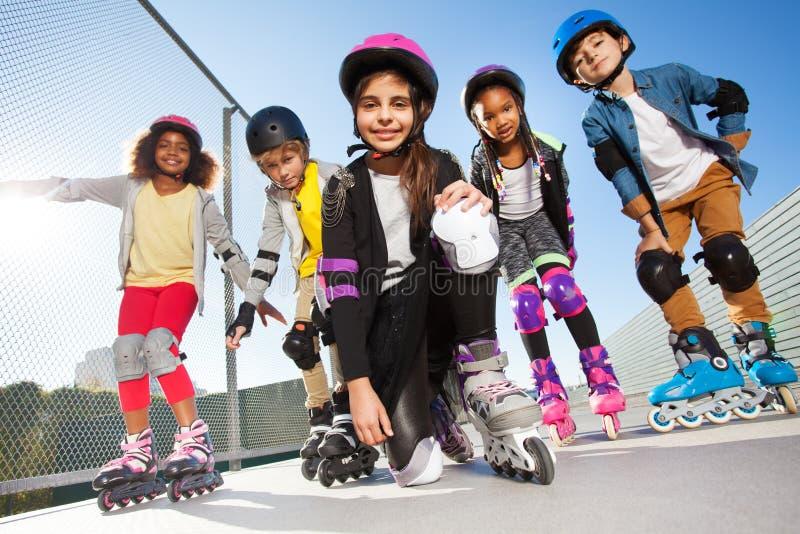 使用与朋友的直排轮式溜冰鞋的女孩户外 库存照片