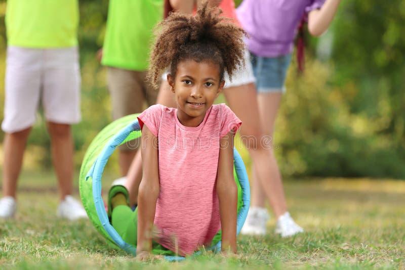 使用与朋友的逗人喜爱的矮小的非裔美国人的孩子 免版税库存照片