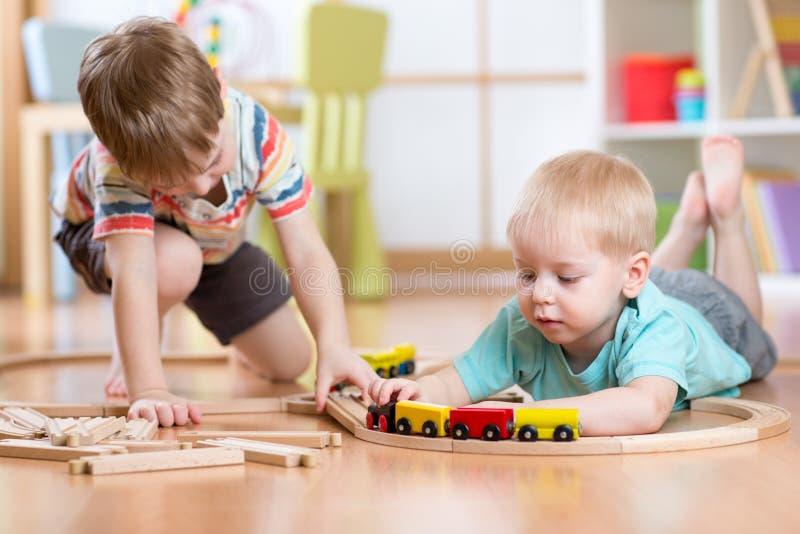 使用与木火车的逗人喜爱的孩子 小孩哄骗与块和火车的戏剧 在家修造玩具铁路的男孩或 库存照片