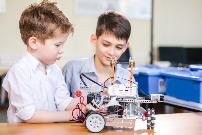 使用与机器人的两个兄弟孩子戏弄在学校机器人学课,室内 免版税库存图片