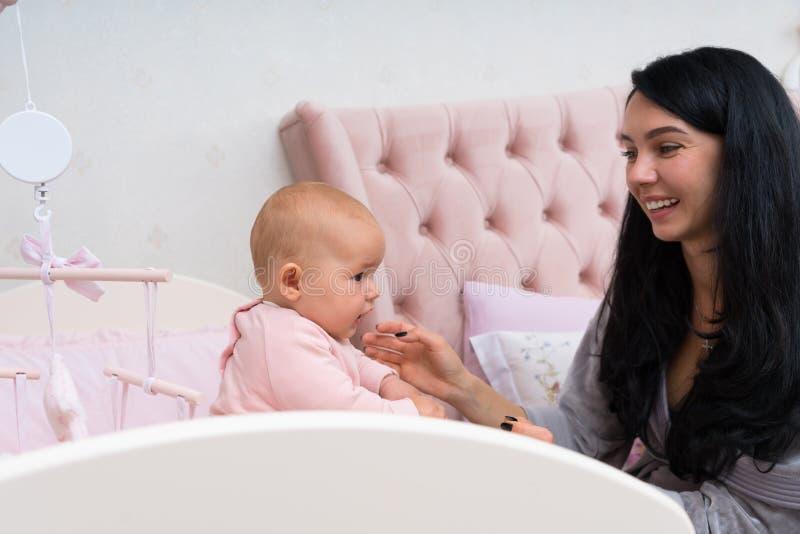 使用与桃红色小儿床的婴孩的愉快的母亲 免版税库存照片