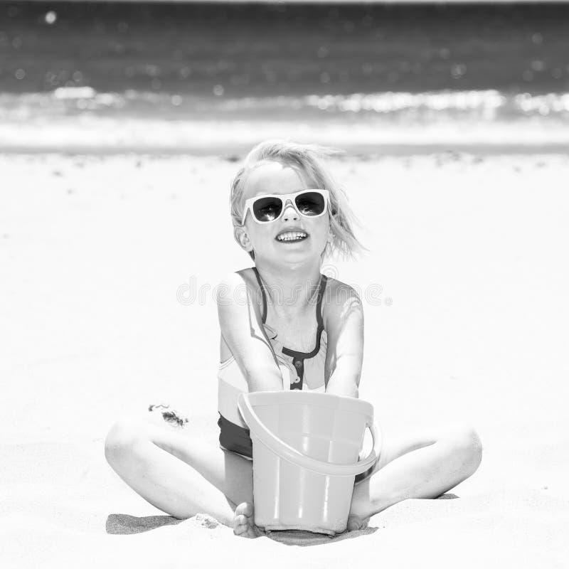 使用与桶的海岸的微笑的现代孩子 库存图片