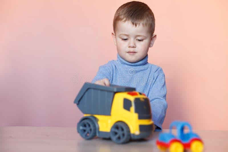 使用与模型汽车汇集的一个逗人喜爱的小男孩 玩具混乱在儿童居室 免版税图库摄影