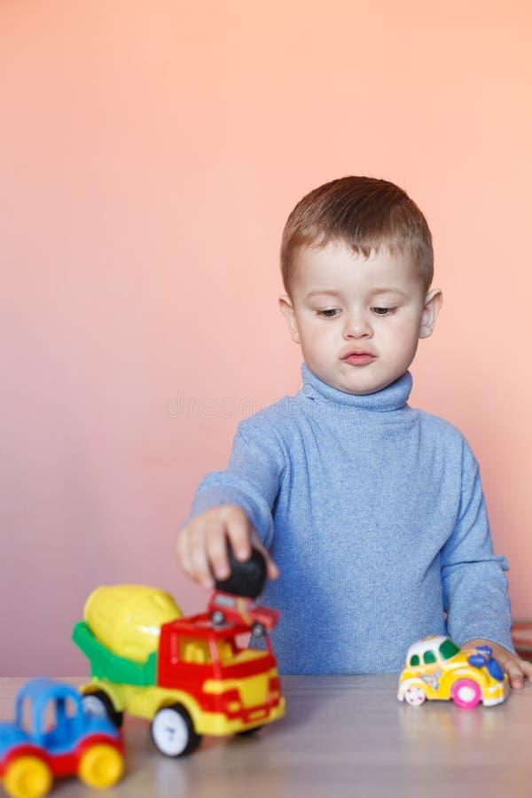 使用与模型汽车汇集的一个逗人喜爱的小男孩 玩具混乱在儿童居室 免版税库存图片
