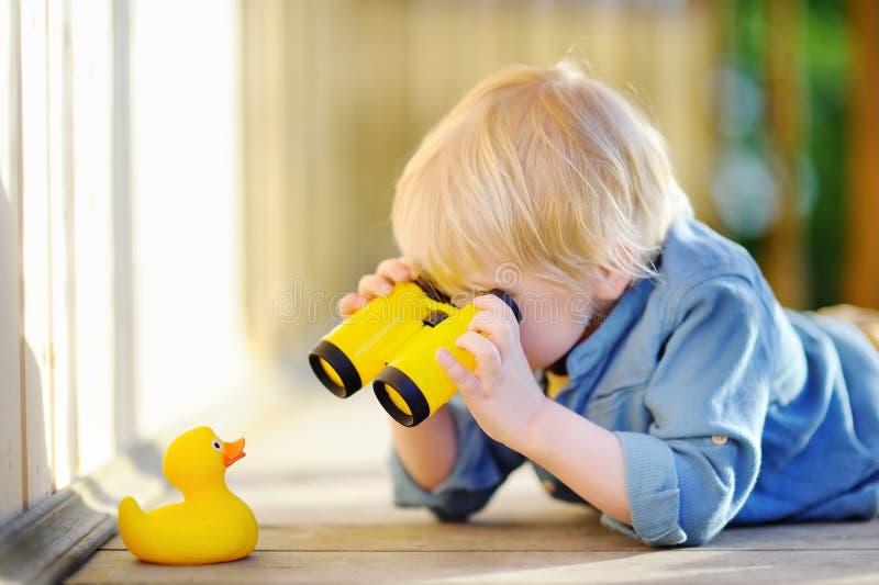 使用与橡胶鸭子和塑料双筒望远镜的逗人喜爱的小男孩户外 库存图片