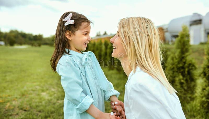 使用与母亲的特写镜头室外画象愉快的孩子 使用和微笑在公园的年轻女人和逗人喜爱的孩子画象  库存照片