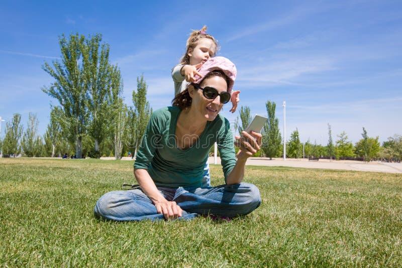 使用与母亲读书电话的孩子在公园 库存照片