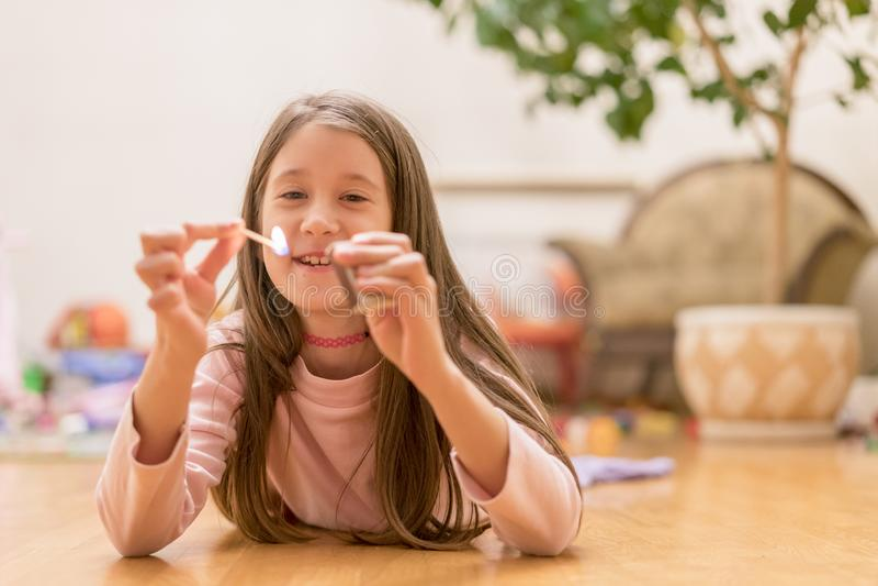 使用与比赛的女孩 处境危险在家 与比赛,火的小儿童游戏,火飘动,危险,孩子 免版税库存照片