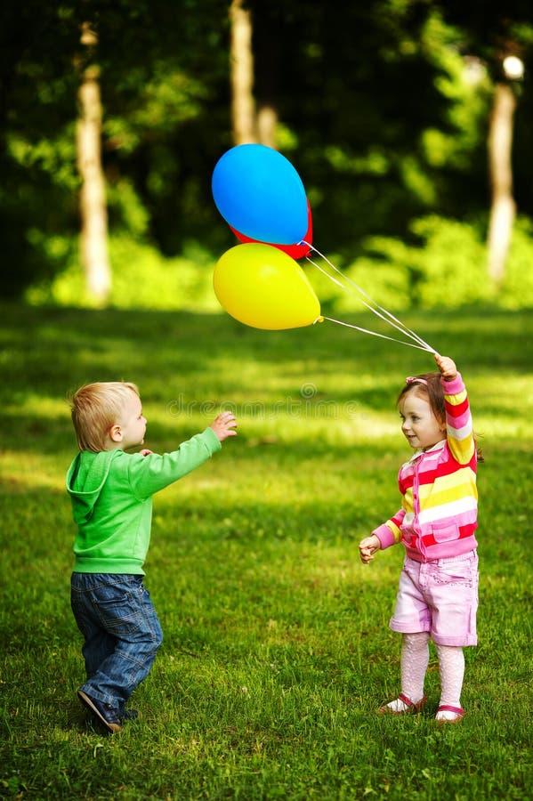 使用与气球的女孩和男孩在公园 免版税库存图片