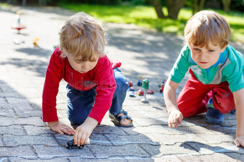 使用与汽车玩具的两个小孩男孩 免版税库存图片