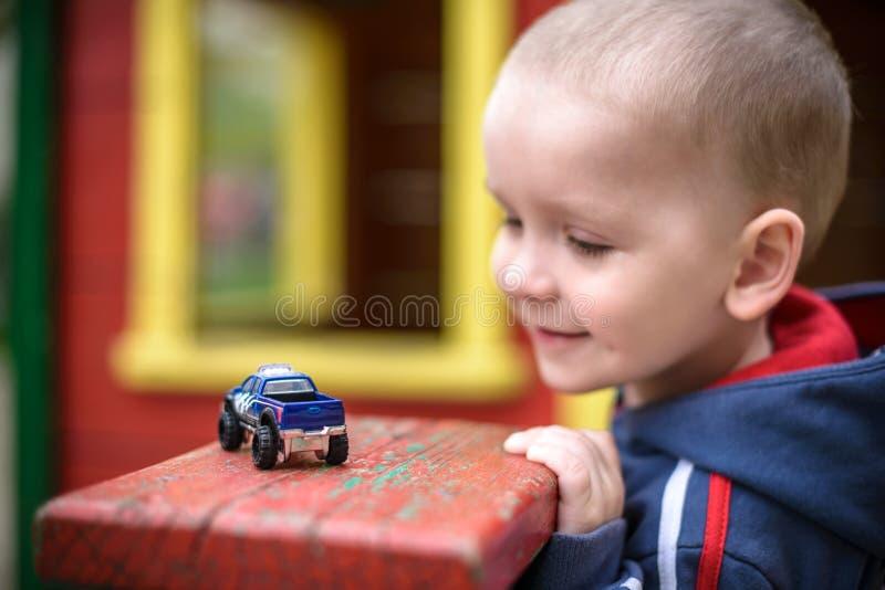 使用与汽车玩具的小小孩男孩 选择聚焦  微笑和获得乐趣 Leasure晚上戏剧儿童概念 免版税库存图片