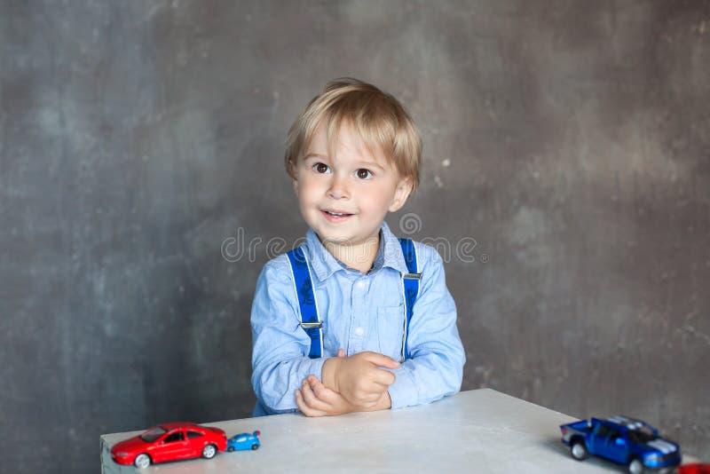 使用与汽车,独立儿童的比赛的一个逗人喜爱的小男孩的画象 使用与玩具汽车的学龄前男孩在幼儿园 免版税库存图片