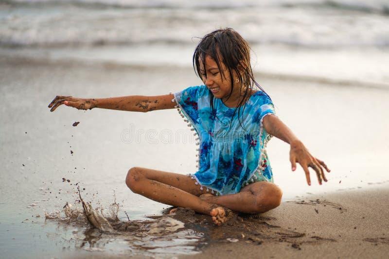使用与沙子的年轻美好和愉快的亚裔美国人混杂的种族儿童女孩7或8岁获得享受夏天的乐趣 免版税图库摄影