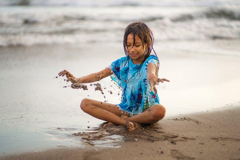 使用与沙子的年轻美好和愉快的亚裔美国人混杂的种族儿童女孩7或8岁获得享受夏天的乐趣 库存图片