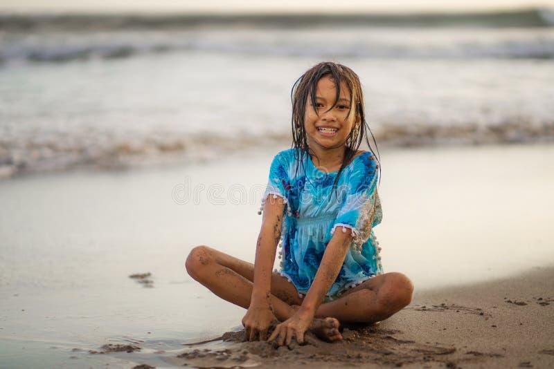 使用与沙子的年轻美好和愉快的亚裔美国人混杂的种族儿童女孩7或8岁获得享受夏天的乐趣 免版税库存照片