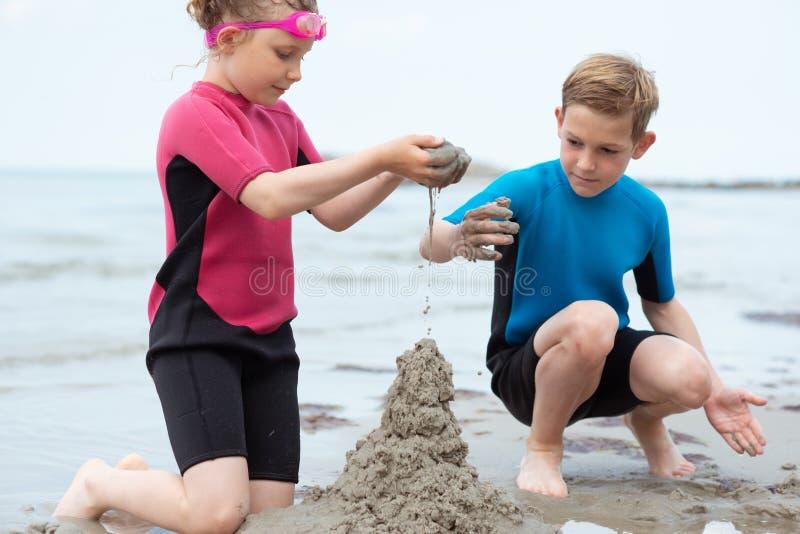 使用与沙子的氯丁胶泳装的两个愉快的兄弟姐妹孩子在海 图库摄影
