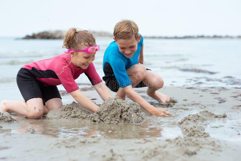 使用与沙子的氯丁胶泳装的两个愉快的兄弟姐妹孩子在海 库存图片