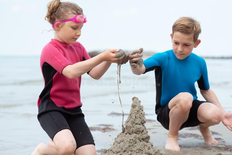 使用与沙子的氯丁胶泳装的两个愉快的兄弟姐妹孩子在海 库存照片